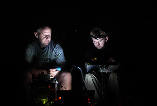 Illuminated only by the computer monitor, Howard remotely pilots an infrared camera around a Pogo nest at Sycamore canyon, with Gavin assisting.